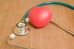 Coeur et stéthoscope rouges sur le fond en bois Photos stock