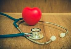 Coeur et stéthoscope rouges sur le fond en bois Images libres de droits