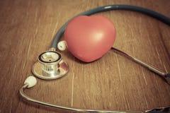 Coeur et stéthoscope rouges sur le fond en bois Photographie stock libre de droits
