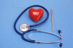 Coeur et stéthoscope rouges sur un fond bleu Photos stock