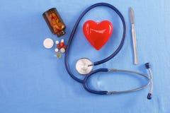 Coeur et stéthoscope rouges sur un fond bleu Photos libres de droits