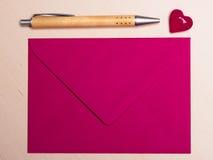 Coeur et stylo roses d'enveloppe sur la table Images stock