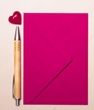 Coeur et stylo roses d'enveloppe sur la table Photo libre de droits
