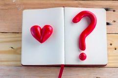 Coeur et symbole rouge de point d'interrogation sur le carnet Images libres de droits