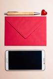 Coeur et téléphone rouges d'enveloppe sur la table Photo libre de droits