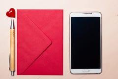 Coeur et téléphone rouges d'enveloppe sur la table Image libre de droits