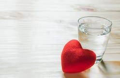 Coeur et verre rouges de l'eau sur en bois pour sain ou le mode de vie Photos libres de droits