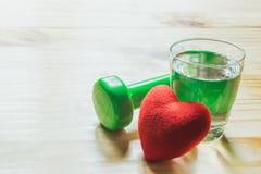 Coeur et verre rouges de l'eau sur en bois pour sain ou le mode de vie Photo stock