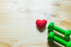 Coeur et verre rouges de l'eau sur en bois pour sain ou le mode de vie Photos stock
