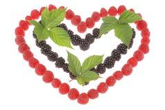 Coeur fabriqué à partir de des framboises et des mûres Feuilles de dessus de bl Photo stock