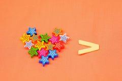 Coeur fait à partir de petites étoiles colorées sur le fond orange, foyer sélectif Photos libres de droits