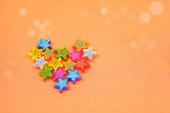 Coeur fait à partir de petites étoiles colorées sur le fond orange, foyer sélectif Image libre de droits