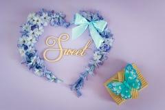 Coeur fait à partir des fleurs de jacinthe avec l'arc en bon état et des boîte-cadeau avec le papillon sur le fond pourpre Image libre de droits