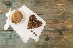Coeur fait à partir des grains de café et de la tasse de café sur le fond en bois Photo libre de droits