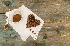 Coeur fait à partir des grains de café et de la tasse de café sur le fond en bois Images libres de droits