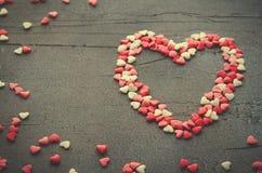 Coeur fait avec de petits coeurs de sucrerie, rose, rouge, couleurs de whie, sur le fond foncé Amour, concept de jour du ` s de V Image libre de droits