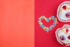 Coeur fait avec de petits coeurs de sucrerie, rose, rouge, couleurs blanches bleues avec deux gâteaux sur le fond rouge Amour, co Image libre de droits