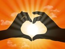 Coeur fait avec des doigts sur le fond de coucher du soleil Photo libre de droits