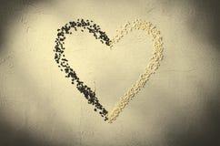 Coeur fait avec les graines de sésame noires et blanches, sur le fond gris Amour, concept de jour du ` s de Valentine Vue supérie Photographie stock