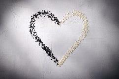 Coeur fait avec les graines de sésame noires et blanches, sur le fond gris Amour, concept de jour du ` s de Valentine Vue supérie Photo libre de droits