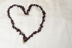 Coeur fait de belles perles femelles, colliers des pierres foncées brunes, ambres sur un fond de tissu beige Images stock
