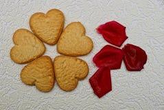 Coeur fait de biscuits et pétales de rose secs sur un backgrou gris Photographie stock libre de droits