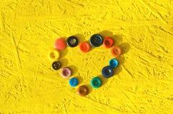 Coeur fait de boutons Le concept de l'amour Fond jaune couture, passe-temps, créatif, antiquités Images libres de droits