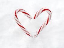 Coeur fait de cannes de sucrerie dans la neige Photo stock