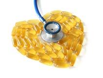Coeur fait de capsules d'huile de poisson avec le stéthoscope photos stock