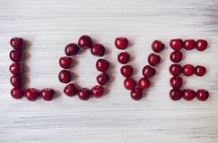 Coeur fait de cerises foncées Fruit rouge sur le fond en bois L'été envoie l'amour Particules d'art Image libre de droits