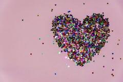 Coeur fait de coeurs confithy en plastique sur un fond rose Résumé images stock