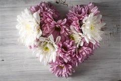 Coeur fait de fleurs sur la vue supérieure de fond en bois blanc Image libre de droits
