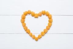 Coeur fait de framboises jaunes sur la table en bois blanche Photos libres de droits