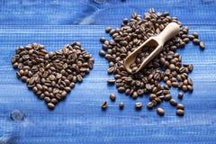Coeur fait de grains de café avec le scoop en bois sur la table en bois bleue Photos libres de droits