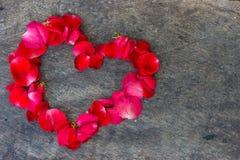 Coeur fait de pétales rouges sur en bois Photographie stock libre de droits