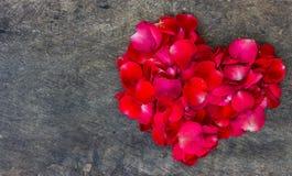 Coeur fait de pétales rouges sur en bois Image stock