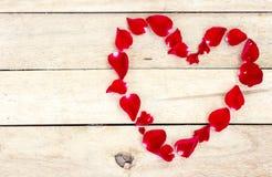 Coeur fait de pétales rouges sur en bois Photo libre de droits