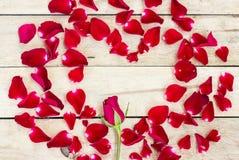 Coeur fait de pétales rouges sur en bois Photos libres de droits