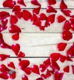 Coeur fait de pétales rouges sur en bois Images libres de droits