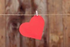 Coeur fait de pose de papier peint sur une corde Images libres de droits
