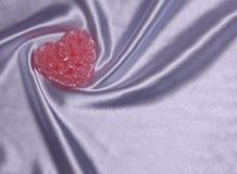 Coeur fait de roses sur le tissu de satin Photo stock