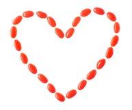Coeur fait de sucreries rouges d'isolement sur le blanc Photographie stock libre de droits