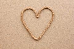 Coeur fait en corde sur le sable Photo stock