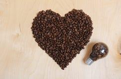 Coeur fait en grains de café et ampoule avec des grains de café à l'intérieur sur un fond en bois clair, vue supérieure Image libre de droits