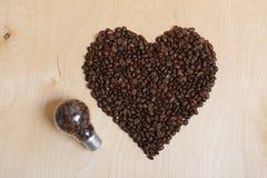 Coeur fait en grains de café et ampoule avec des grains de café à l'intérieur sur un fond en bois clair, vue supérieure Photo stock