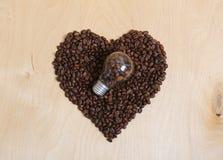 Coeur fait en grains de café et ampoule avec des grains de café à l'intérieur sur un fond en bois clair, vue supérieure Photos stock
