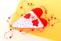 Coeur fait main de feutre - symbole de jour de valentines, de jouet blanc et rouge de feutre de coeur sur le fond jaune Image libre de droits