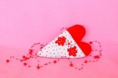Coeur fait main de feutre - symbole de jour de valentines, de jouet blanc et rouge de feutre de coeur sur le fond rose Photographie stock