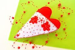 Coeur fait main de feutre - symbole de jour de valentines, de jouet blanc et rouge de feutre de coeur sur le fond vert Images stock
