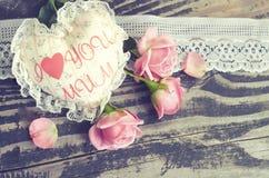 Coeur fait main de textile avec la maman d'amour de l'inscription I et les pétales de roses rouges sur un fond en bois Un thème h Photo stock